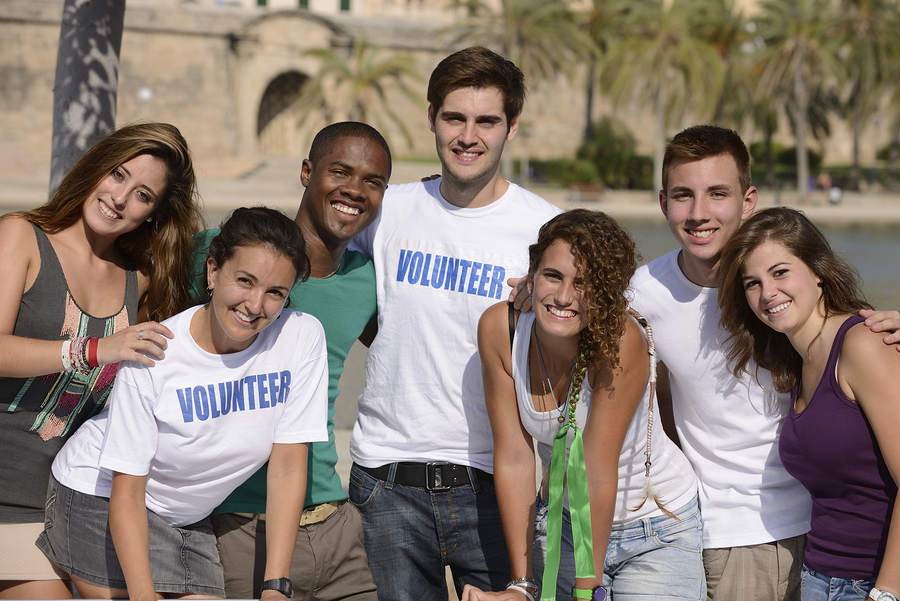 happy and diverse volunteer group smiling outdoors